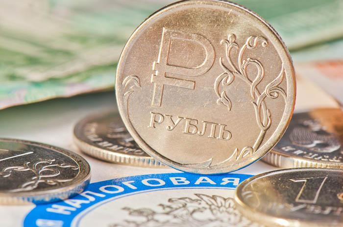Рубль. Монеты и купюры рядом с логотипом федеральной налоговой службы